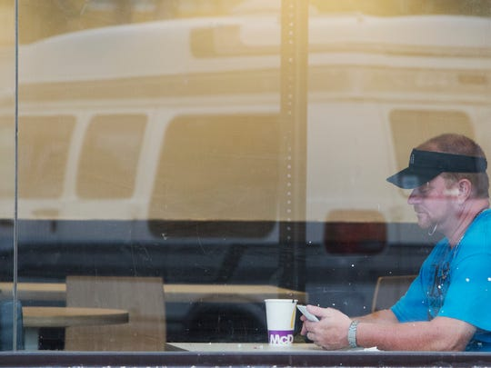 Drew Broderick passes the time at a North Fort Myers McDonalds in July of this year. The construction worker, who is considered homeless spends as much time as he can seeking out air conditioning and other modern amenities. The van in the reflection is one his homes.