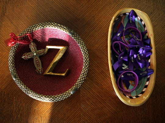 Elvin and Cheryl Daniel keep a bowl on their coffee table with a cross, a ÒZ,Ó and a basket of ribbons and bracelets in Zina HaughtonÕs favorite color, purple, to remember Elvin's slain sister. Haughton was murdered by her estranged husband with a gun he purchased via Armslist.com, despite having a restraining order against him.