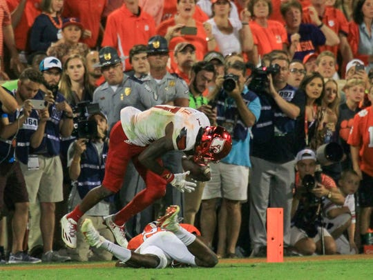 A crowd and photographers look on as Clemson cornerback