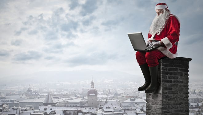 Santa Claus is using a laptop on the top of a house