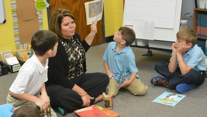 South Grant Elementary third-grade teacher Marleen Jones reads a book to her class on the first day of school. Jones asked her students to bring their favorite book to school Friday.