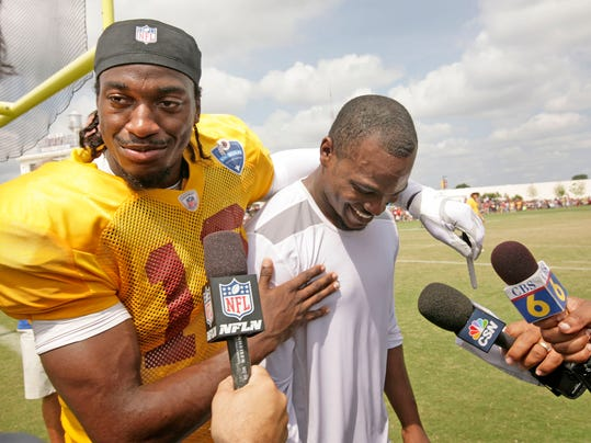 Washington Redskins NFL football team quarterback Robert Griffin III (10) hugs New England Patriots' Josh Boyce (82) after a joint team practice in Richmond, Va., Monday, Aug. 4, 2014. The two went to high school and church together in Richmond, Va. (AP Photo/Jay Paul)