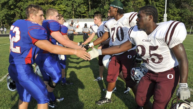 Mason and Okemos football captains shake hands before a season-opening game at  Mason Aug. 24, 2012. The two teams face off again Thursday in this year's season opener.