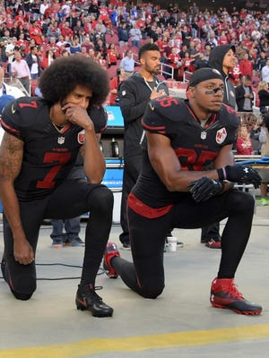 Colin Kaepernick (7) and Eric Reid (35) kneel before a 49ers game Oct. 6, 2016, in protest during the national anthem. The NFL has adopted a new policy requiring players stand during the anthem.