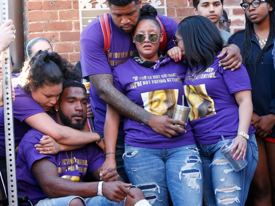 Marcus Martin, bottom left, pauses during a vigil on Sunday, Aug. 13, 2017, held for the victims of an attack on Saturday in Charlottesville, Va. A car plowed into a crowd of people protesting a white supremacist rally on Saturday, injuring over a dozen people including Martin.