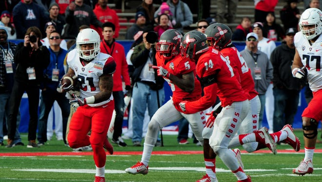 Arizona Wildcats running back Orlando Bradford (21) carries the ball as New Mexico Lobos safety Lee Crosby (5) and safety Daniel Henry (14) defend during the second half in the 2015 New Mexico Bowl at University Stadium.