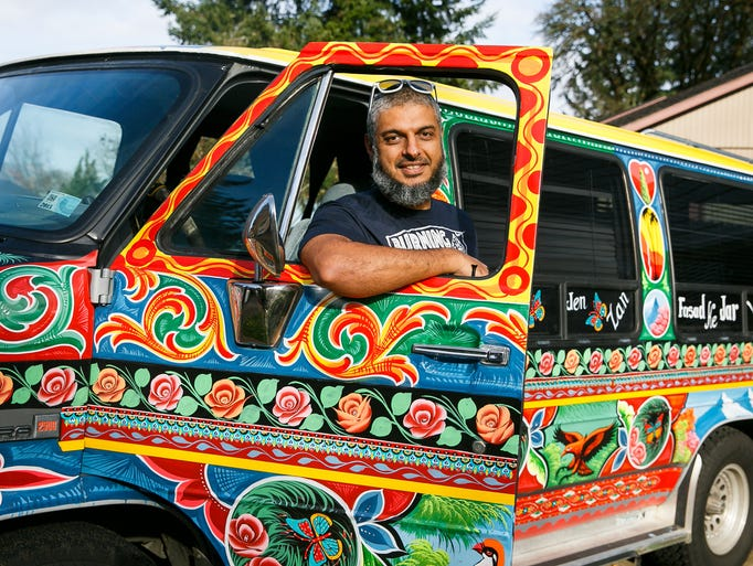 Fahd Saeed stands with his van that was painted by