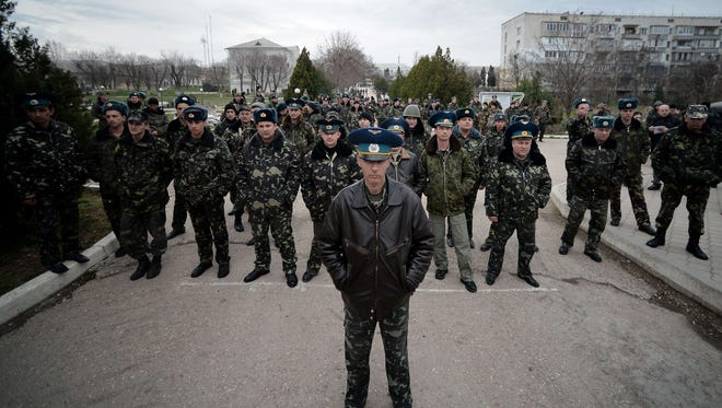 Sevastopol Air Base second in command Olieg Podapalov, along with his men, face pro-Russian protesters demonstrating outside the base in Belbek, Ukraine, on Thursday.