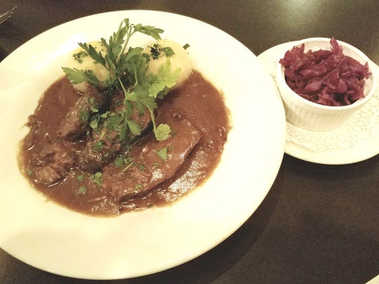 Ethan's Grill's Sauerbraten  a traditional dish of marinated and braised beef served with red cabbage and potato dumplings.