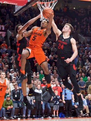 Florida guard KeVaughn Allen, center, shoots over Gonzaga forward Corey Kispert, right, and forward Johnathan Williams, left, during the second half of their PK80 game.