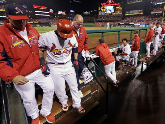 St. Louis Cardinals' Yadier Molina is helped down the stairs toward the clubhouse after being injured  in Game 2 of the National League baseball championship series against the San Francisco Giants Sunday, Oct. 12, 2014, in St. Louis. (AP Photo/David J. Phillip)
