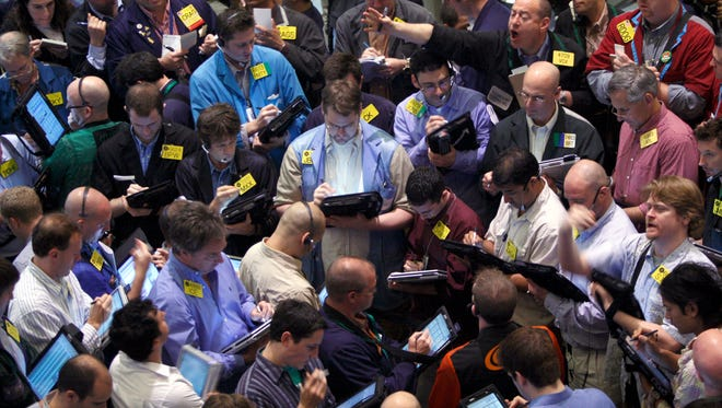 FILE - In this April 21, 2008 file photo, traders deal crude oil options on the floor of the New York Mercantile Exchange. Most pits in Chicago and New York where traders bet on future prices of palladium and gold, cattle and corn and dozens of other commodities are expected to close for good on Monday, July 6, 2015. (AP Photo/Jin Lee, File)