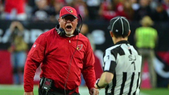 Arizona Cardinals head coach Bruce Arians reacts as NFL side judge Scott Novak (1) looks on during the second half  at University of Phoenix Stadium.