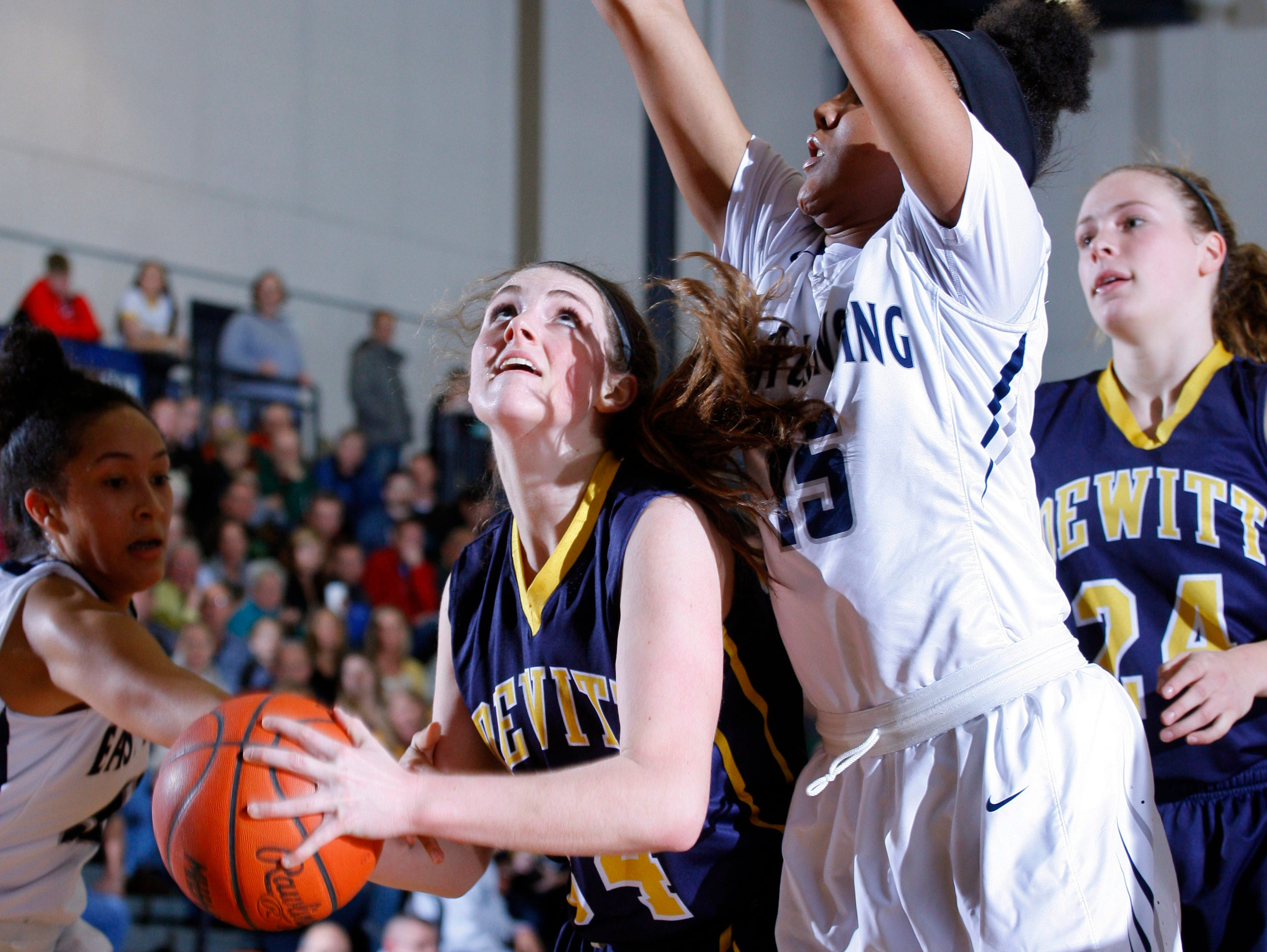 DeWitt's Grace George, center, looks for a shot against the defense of East Lansing's Jaida Hampton, right, and Aaliyah Nye, left, during their district final game Friday, March 3, 2017, in East Lansing, Mich. East Lansing won 48-47.