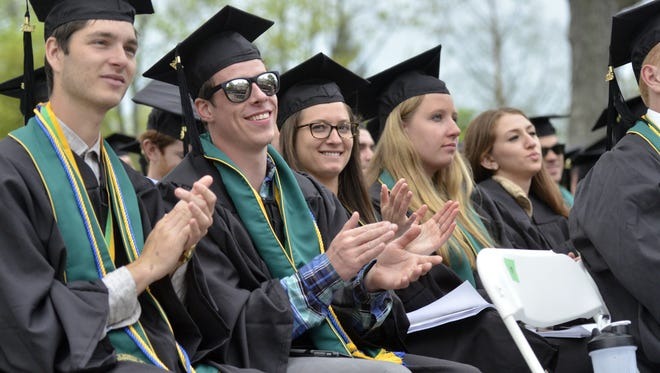 Graduates in the University of Vermont's class of 2016 clap during a speech during commencement Sunday on the university's green.