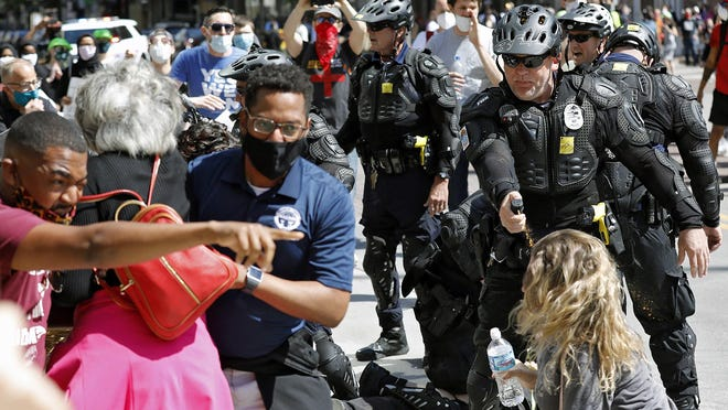 Columbus City Council President Shannon Hardin, pointing at left, was pepper-sprayed by police during a Downtown protest in May. With him are Franklin County Commissioner Kevin Boyce, center, and Congresswoman Joyce Beatty, between them with back turned.