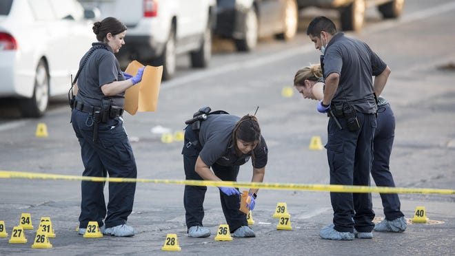 Crime scene investigators pick up evidence after Austin police officers shot Aquantis Griffin, 21, at Sixth and Trinity streets on Aug. 17, 2018. Griffin's family is suing the city of Austin, saying that footage from the officers' body-worn cameras contradicts the Austin police account that Griffin pointed his gun at them.