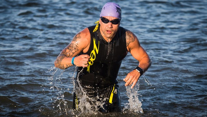 Michael Mendoza transitions from the 1.2 mile swim to the 56 mile bike ride during Ironman 70.3 at the Prairie Creek Reservoir Saturday morning. Mendoza, who is a former Marine sniper and was critically injured by a grenade while serving overseas in 2006, has his sights set on beating the world record for completed half Ironmans in a year.