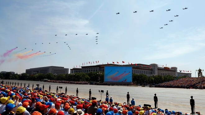 Chinese military helicopters fly by a parade commemorating the 70th anniversary of Japan's surrender during World War II held in front of Tiananmen Gate in Beijing, Thursday, Sept. 3, 2015, on a day with clear blue skies.