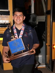Deming High junior Luis Burke was all smiles when he stepped off the bus at 3:20 a.m. Sunday morning hold the state championship blue trophy.
