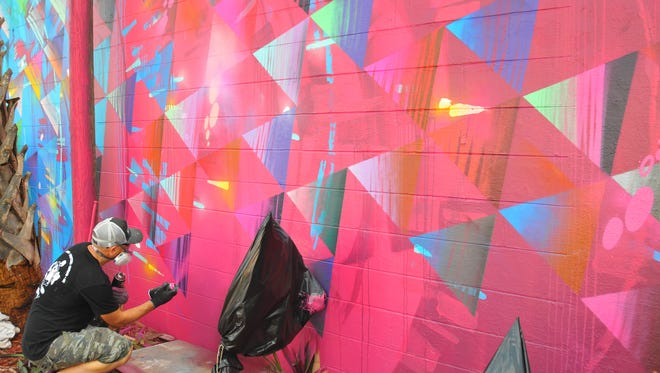 Miami artist and muralist Jay Bellicchi works on a large mural on the west wall of Debauchery in downtown Melbourne, facing Matt's Casbah.