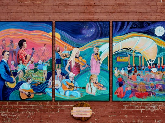 """A mural in tribute to Shindig on the Green was unveiled on April 21, followed by a performance from the musicians and dancers depicted in the work. Doreyl Ammons Cain's """"Golden Threads"""" hangs on the North-facing wall outside Pack's Tavern."""