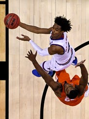 Kansas Jayhawks guard Devonte' Graham drives against