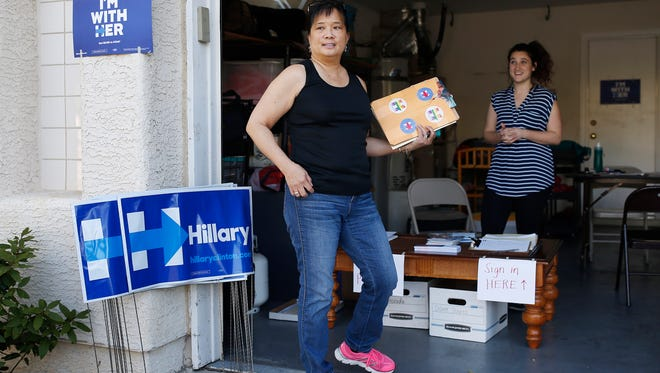 In this Feb. 12, 2016, photo, Cynthia Ameli, center, a Chinese-American, picks up materials from Sarah Gibson before heading out to canvass for presidential candidate Hillary Clinton in Las Vegas. Asian-American voters are the fastest-growing racial group in the U.S. and both parties increasingly are wooing them.