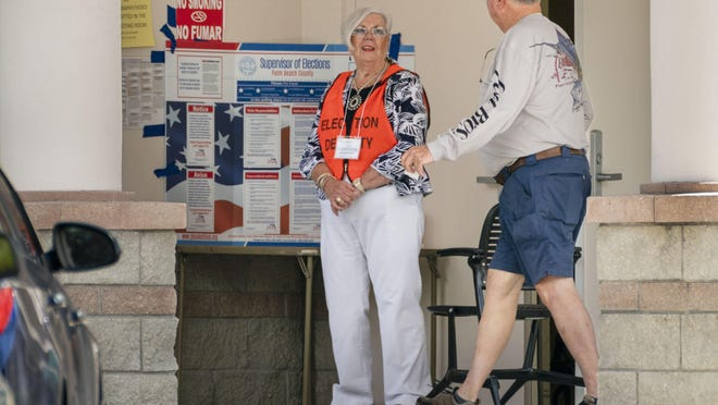 Poll worker Kathleen Fahey greets a voter after he casts his ballot during early voting at the county's Palm Beach Gardens branch library Saturday. Early voting continues through 6 p.m. Sunday at 16 county locations.