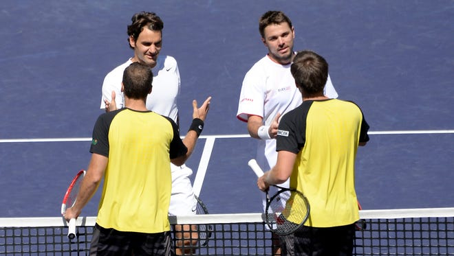 Roger Federer, top left, and Stanislas Wawrinka, top right, shake hands after their doubles match against Alexander Peya and Bruno Soares at the BNP Paribas Open.