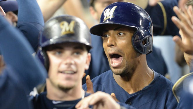 Brewers left fielder Khris Davis is greeted in the dugout after scoring a run in the eighth inning at Dodger Stadium.