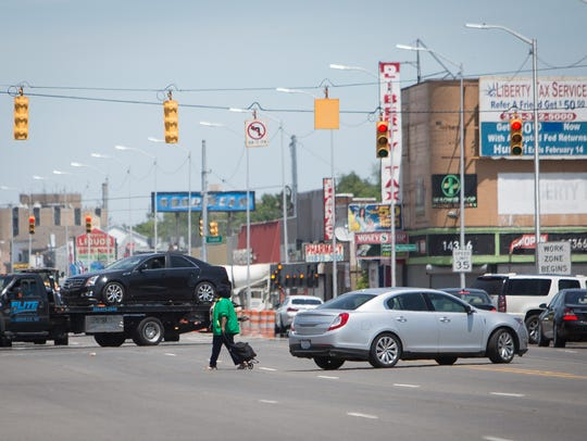A pedestrian crosses Gratiot Avenue in Detroit on Tuesday, June 26, 2018. The stretch of Gratiot Avenue between Greiner Street and  East Seven Mile Road has been the site of numerous pedestrian fatalities.