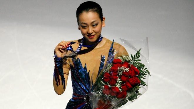 Mao Asada of Japan raises her first place medal during the award ceremony in the ladies free skate event at Joe Louis Arena.