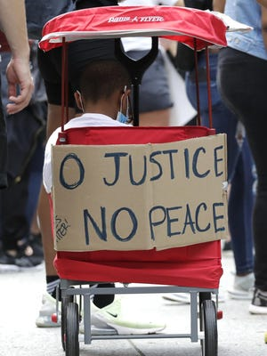 A sign is seen on a kids folding wagon during people demonstrate in Chicago, Friday, June 19, 2020, to mark Juneteenth, the holiday celebrating the day in 1865 that enslaved black people in Galveston, Texas, learned they had been freed from bondage, more than two years after the Emancipation Proclamation.