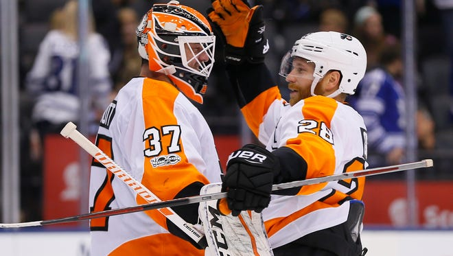 Claude Giroux (28) congratulates goaltender Brian Elliott (37) on a win over the Toronto Maple Leafs.