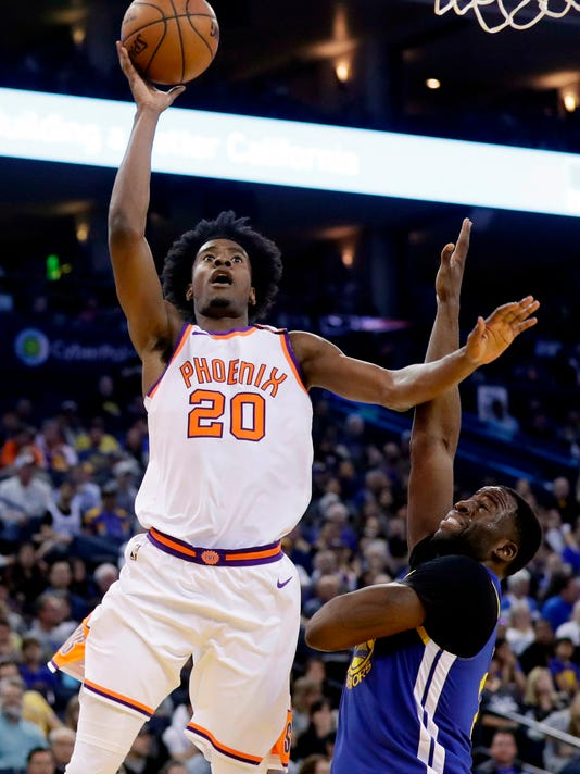 FILE - In this April 1, 2018, file photo, Phoenix Suns' Josh Jackson (20) shoots over Golden State Warriors' Draymond Green during the second half of an NBA basketball game in Oakland, Calif. For the eighth season in a row, the Suns won't make the playoffs. Devin Booker, T.J. Warren and rookie Jackson form the core of the young talent the Suns have accumulated. (AP Photo/Marcio Jose Sanchez, File)