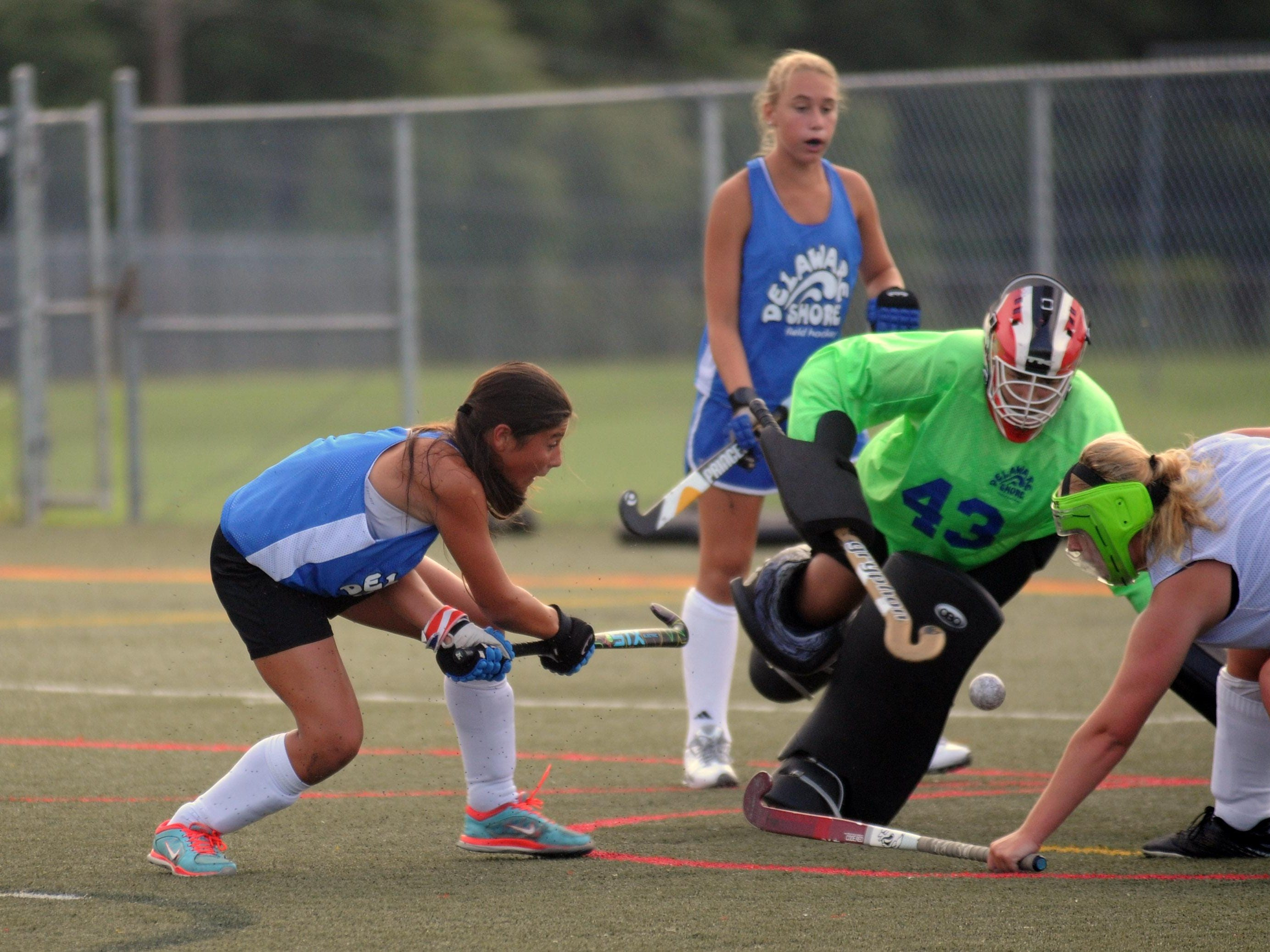 Players converge on the ball and goalie during a summer league game for Delaware Shore Field Hockey at Cape Henlopen High School. Some of these players will be traveling with the U14 team to Disney World.
