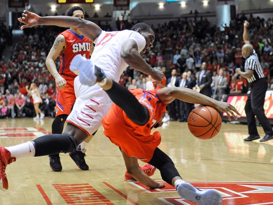Houston's Bertrand Nkali, left, and SMU's Ben Moore chase a loose ball during the second half of an NCAA college basketball game Monday, Feb. 1, 2016, in Houston. Houston won 71-68 for an upset. (AP Photo/Pat Sullivan)