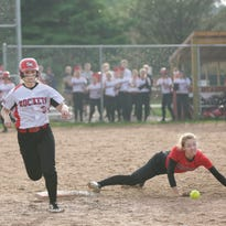 Spencer's Sadie Mercier makes it to first base despite an attempted catch by Marathon's Amanda Kind during the WIAA regional finals at Spencer May 27, 2016.