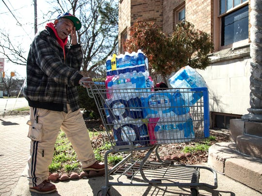 """Flint resident Joe Willie Whiteside, 80, takes a break after pushing a cart full of bottled water almost a mile from the pickup point where a Flint resident leaves it out for the neighborhood in March 2016 in downtown Flint. """"If it wasn't for this I couldn't have water. I've got to use the shopping cart because I don't drive."""" He makes the trip twice a week to gather cases of bottled water that a person leaves out for the neighborhood in downtown Flint. Whiteside, who has a stent in his heart and screws in his ankle from an injury when he was younger, gathers the water for himself, his wife, grandkids and cat to drink, cook and bathe with. """"If I didn't have the heart problem it wouldn't be as rough on me. I try not to stop and try to get home in a hurry. It's so dangerous out here, especially for a person my age. They think you have money. I don't know what we'd do if these people weren't setting the water out for us. I can't afford to go to the store and get it."""""""