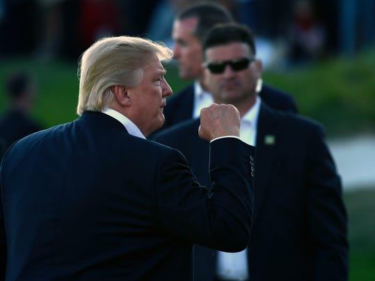 President Donald Trump gestures as he walks over to present the Presidents Cup to the U.S. team in Jersey City, N.J., Sunday, Oct. 1, 2017. (AP Photo/Susan Walsh)