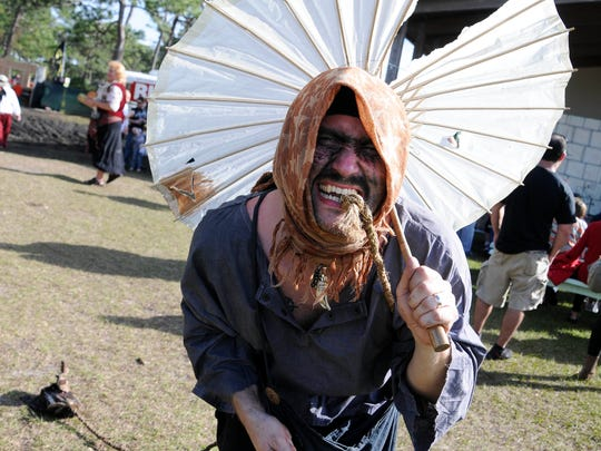 A performer entertains the crowd around the amphitheater on the first day of the Brevard Renaissance Fair in Wickham Park