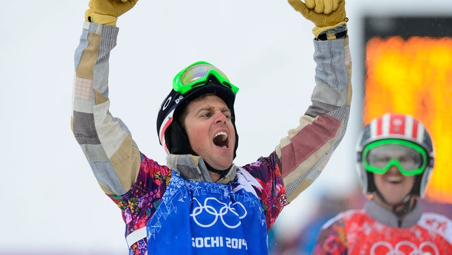 Alex Deibold (USA), blue, reacts during the semifinal run of the men's snowboardcross during the Sochi 2014 Olympic Winter Games at Rosa Khutor Extreme Park.