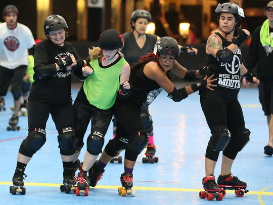 V Town Roller Derby Dame teammates Alma Cervantes (Nightmare on Alm Street #24), from right, Golly Ochoa (Whiskey Whip #7) and Patricia Dondero keep jammer Laura Anderson (ActiFist #314) from advancing past during a scrimmage at Roller Towne in Visalia.