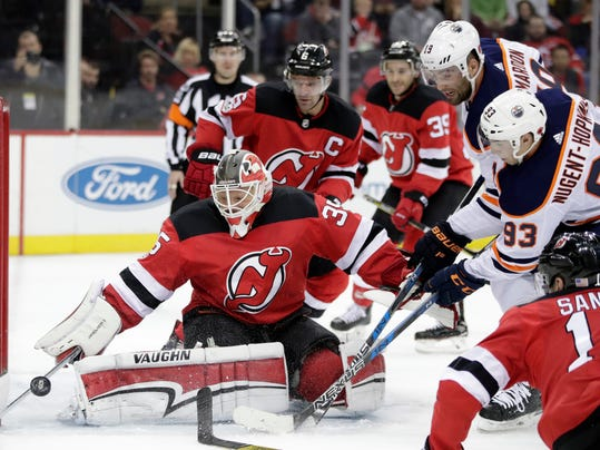 New Jersey Devils goalie Cory Schneider (35) deflects a shot as Edmonton Oilers center Ryan Nugent-Hopkins (93) and left wing Patrick Maroon (19) attack during the first period of an NHL hockey game, Thursday, Nov. 9, 2017, in Newark, N.J. (AP Photo/Julio Cortez)