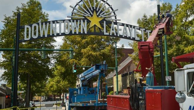 Work crew installs Downtown Lafayette Sign on Jefferson Street. August 24, 2016.