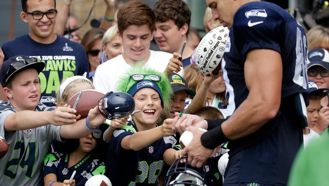 Seattle Seahawks fans reach toward Jimmy Graham for an autograph after an NFL football training camp Monday, Aug. 3, 2015, in Renton, Wash.