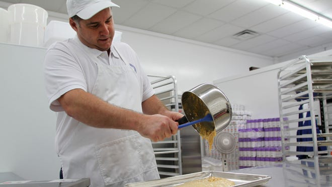 Robert Page pours a batch of coconut brittle in the kitchen of his new store in Genoa Township on Tuesday, May 2, 2017.