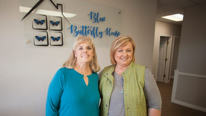 Suzun Abbott and Debbie Heisler work on the finishing touches at the Blue Butterfly House Thursday, April 12, 2018.