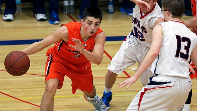 Jordan McCabe of Kaukauna tries to get away from Appleton East's Trent Brunker and Austin Meyer (13) during a Fox Valley Association boys' basketball game on Jan. 27.